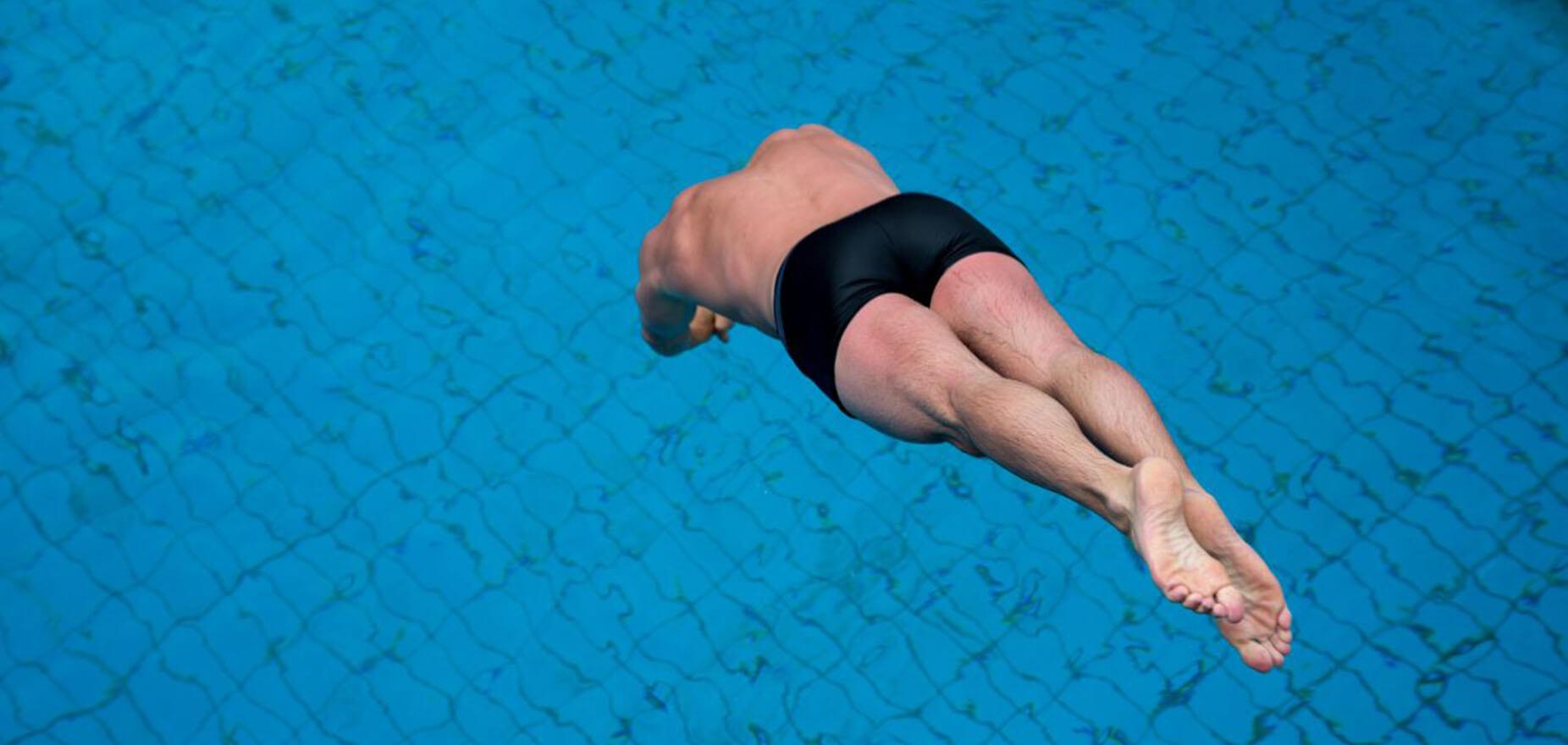 Schwimmer springt in das Schwimmbecken
