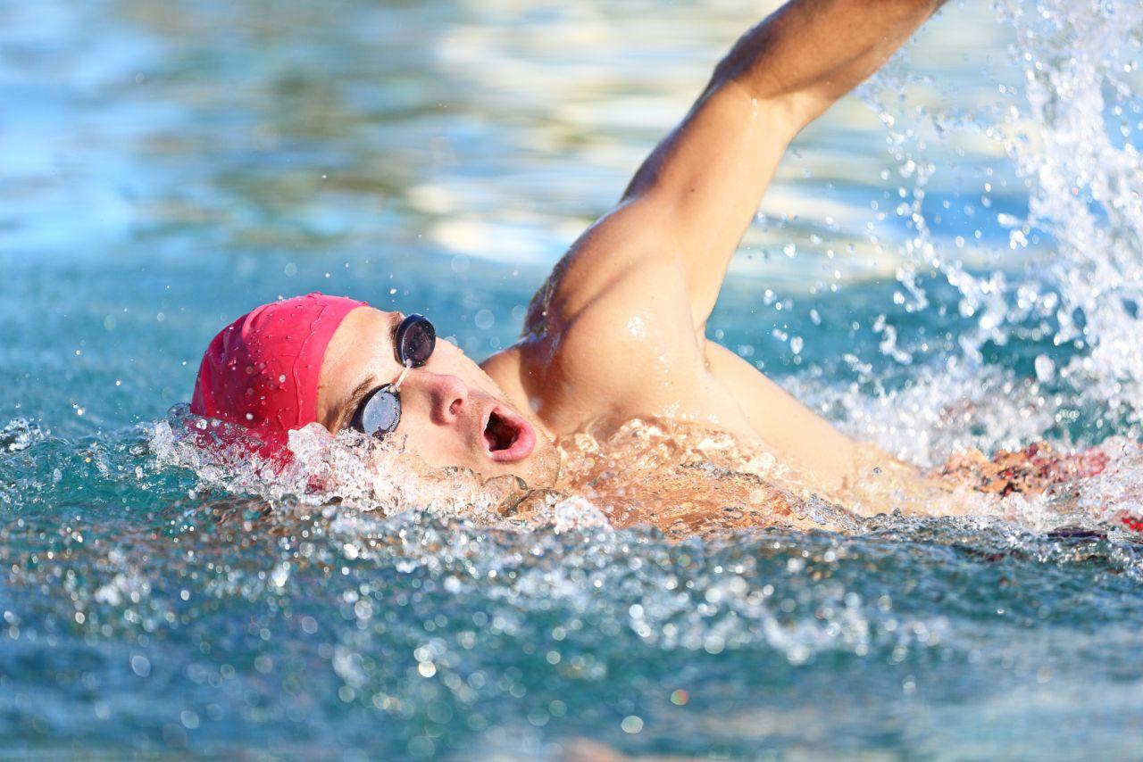 Mann im Schwimmbad mit Badekappe Kraulschwimmen